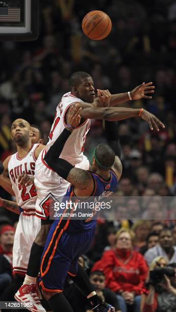 Jimmy Butler of the Chicago Bulls fouls Carmelo Anthony of the New York Knicks at the United Center on April 10 2012 in Chicago Illinois The Bulls...