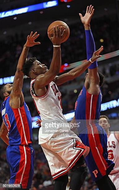 Jimmy Butler of the Chicago Bulls goes up for a shot between Marcus Morris and Andre Drummond of the Detroit Pistons on his way to a gamehigh 43...