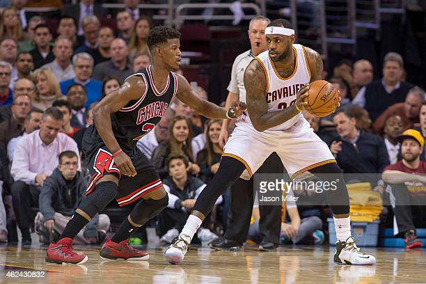 Jimmy Butler of the Chicago Bulls guards LeBron James of the Cleveland Cavaliers during the first half at Quicken Loans Arena on January 19 2015 in...