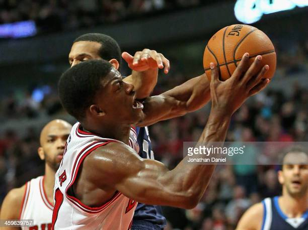 Jimmy Butler of the Chicago Bulls is fouled while shooting by Brandon Wright of the Dallas Mavericks at the United Center on December 28 2013 in...