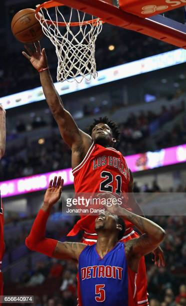Jimmy Butler of the Chicago Bulls leaps over Kentavious CaldwellPope of the Detroit Pistons to block a shot at the United Center on March 22 2017 in...