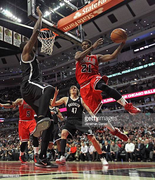 Jimmy Butler of the Chicago Bulls leaps to pass around Andray Blatche of the Brooklyn Nets at the United Center on February 13 2014 in Chicago...