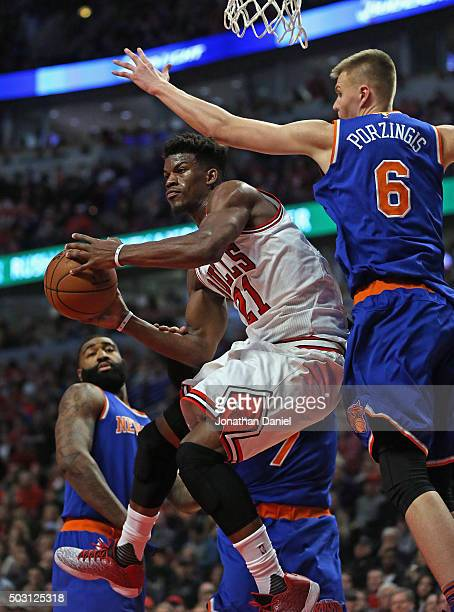 Jimmy Butler of the Chicago Bulls leaps to pass under Kristaps Porzingis of the New York Knicks at the United Center on January 1 2016 in Chicago...