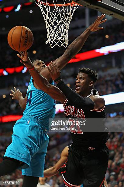 Jimmy Butler of the Chicago Bulls passes around Jason Maxiell of the Charlotte Hornets at the United Center on March 23 2015 in Chicago Illinois The...