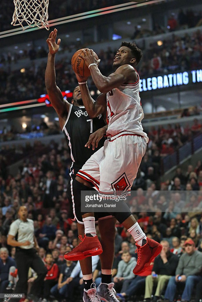 Jimmy Butler #21 of the Chicago Bulls puts up a shot against Joe Johnson #7 of the Brooklyn Netson his way to a game-high 24 points at the United Center on December 21, 2015 in Chicago, Illinois. The Nets defeated the Bulls 105-102.