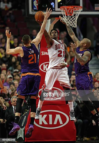 Jimmy Butler of the Chicago Bulls puts up a shot between Alex Len and PJ Tucker of the Phoenix Suns at the United Center on February 21 2015 in...