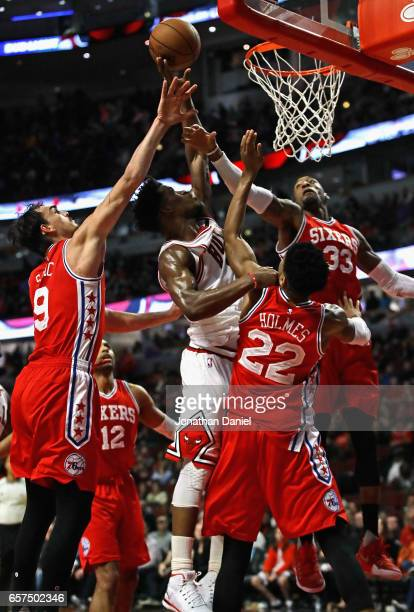Jimmy Butler of the Chicago Bulls puts up a shot between Dario Saric Richaun Holmes and Robert Covington of the Philadelphia 76ers on his way to a...
