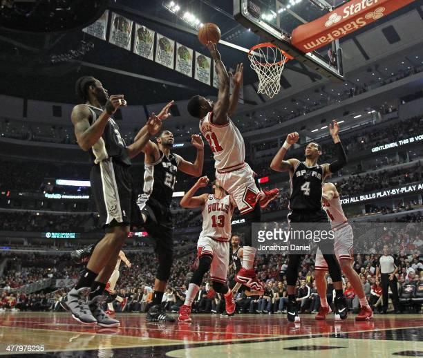 Jimmy Butler of the Chicago Bulls puts up a shot between Kawhi Leonard Tim Duncan and Danny Green of the San Antonio Spurs at the United Center on...