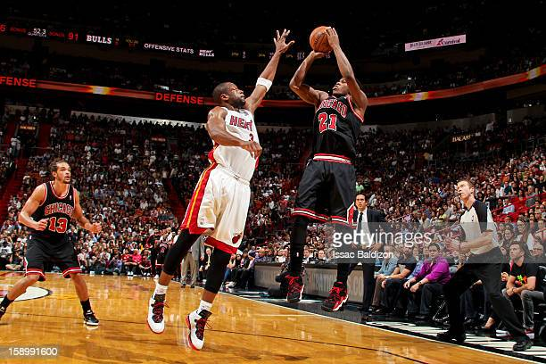 Jimmy Butler of the Chicago Bulls shoots against Dwyane Wade of the Miami Heat on January 4 2013 at American Airlines Arena in Miami Florida NOTE TO...