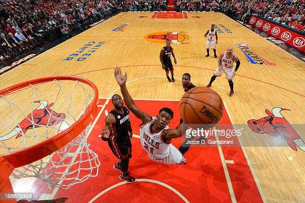 Jimmy Butler of the Chicago Bulls shoots against Dwyane Wade of the Miami Heat in Game Four of the Eastern Conference Semifinals during the 2013 NBA...