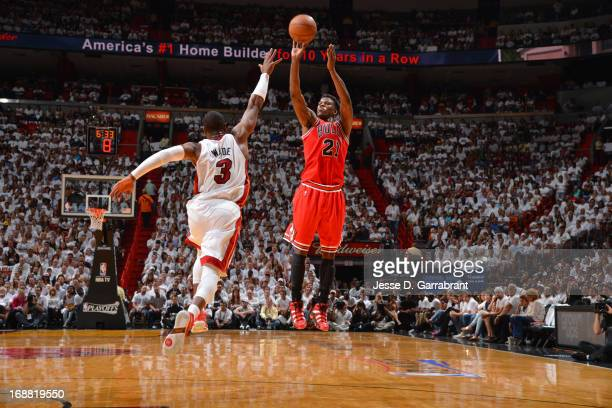 Jimmy Butler of the Chicago Bulls shoots against Dwyane Wade of the Miami Heat in Game Five of the Eastern Conference Semifinals during the 2013 NBA...