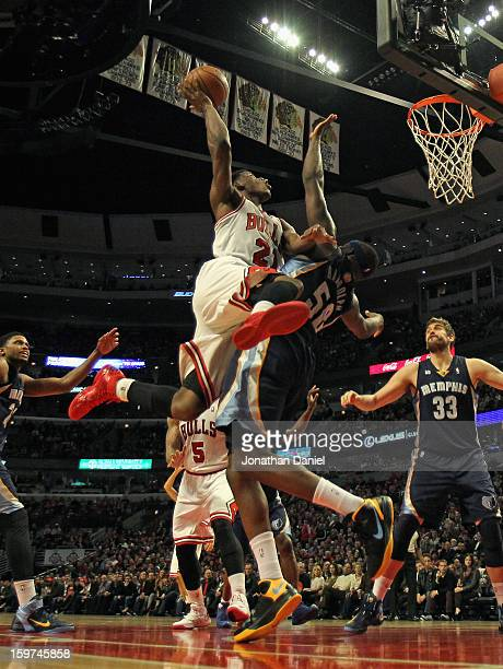 Jimmy Butler of the Chicago Bulls shoots against Zach Randolph of the Memphis Grizzles at the United Center on January 19 2013 in Chicago Illinois...