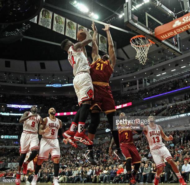 Jimmy Butler of the Chicago Bulls shoots over Andrew Bynum of the Cleveland Cavaliers at the United Center on November 11 2013 in Chicago Illinois...