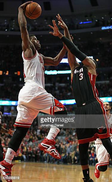 Jimmy Butler of the Chicago Bulls shoots over Dwyane Wade of the Miami Heat at the United Center on March 9 2014 in Chicago Illinois The Bulls...