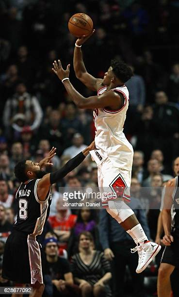 Jimmy Butler of the Chicago Bulls shoots over Patty Mills of the San Antonio Spurs at the United Center on December 8 2016 in Chicago Illinois The...