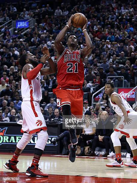 Jimmy Butler of the Chicago Bulls shoots the ball as DeMarre Carroll of the Toronto Raptors defends during an NBA game at the Air Canada Centre on...