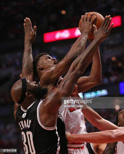 Jimmy Butler of the Chicago Bulls shoots under pressure from Reggie Evans of the Brooklyn Nets in Game Six of the Eastern Conference Quarterfinals...