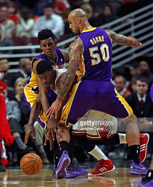 Jimmy Butler of the Chicago Bulls tries to get between Manny Harris and Robert Sacre of the Los Angeles Lakers at the United Center on January 20...