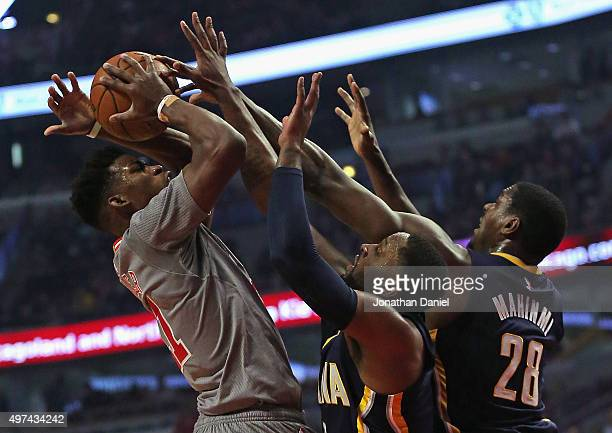 Jimmy Butler of the Chicago Bulls tries to get off a shot under pressure from CJ Miles and Ian Mahinmi of the Indiana Pacers at the United Center on...