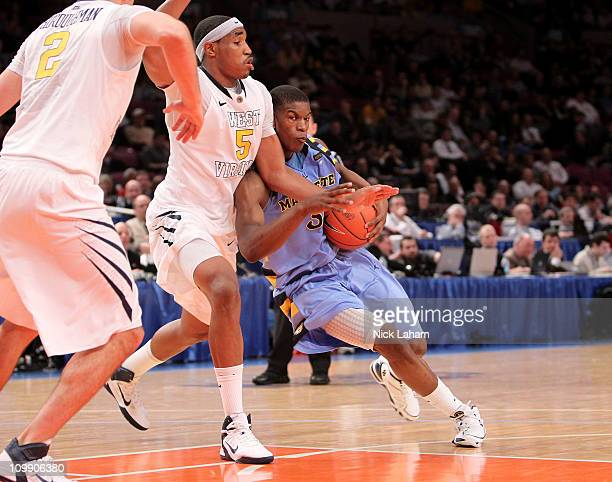 Jimmy Butler of the Marquette Golden Eagles tries to dribble around Kevin Jones of the West Virginia Mountaineers during the second round of the 2011...