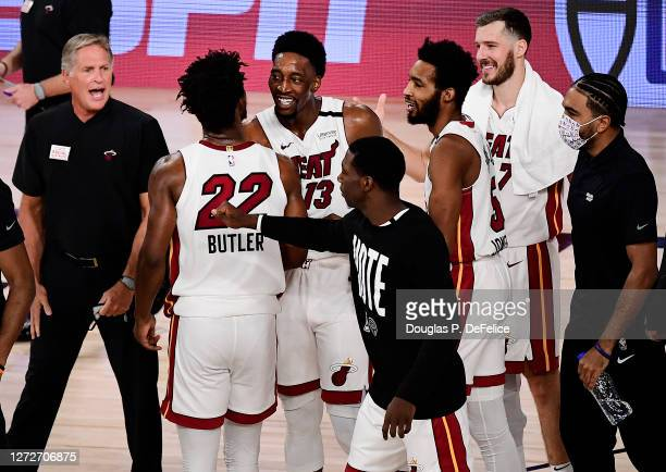 Jimmy Butler of the Miami Heat and Bam Adebayo of the Miami Heat react after their win over Boston Celtics during overtime in Game One of the Eastern...