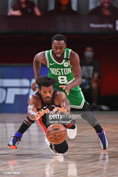 Jimmy Butler of the Miami Heat dives for a loose ball while guarded by Kemba Walker of the Boston Celtics during Game Four of the Eastern Conference...