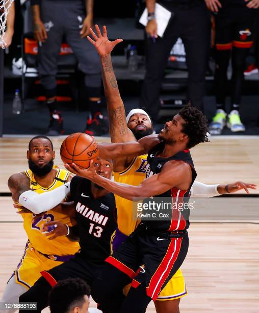 Jimmy Butler of the Miami Heat drives on Markieff Morris of the Los Angeles Lakers as Bam Adebayo of the Miami Heat and LeBron James of the Los...