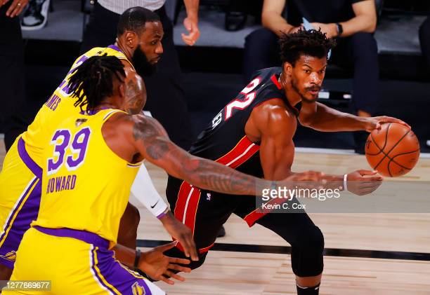 Jimmy Butler of the Miami Heat drives the ball past LeBron James of the Los Angeles Lakers and Dwight Howard of the Los Angeles Lakers during the...