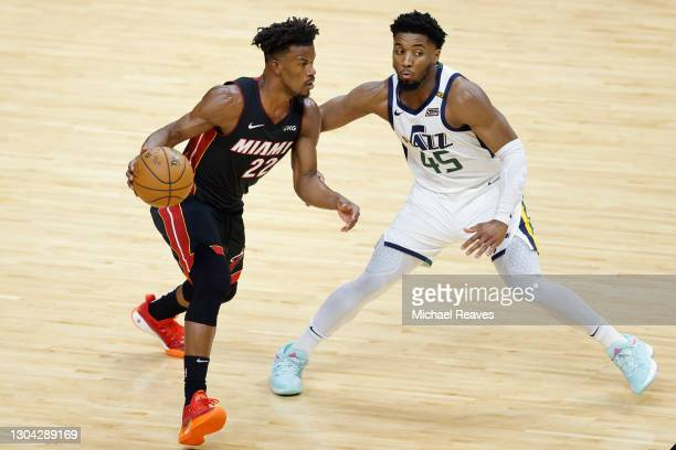 Jimmy Butler of the Miami Heat drives to the basket against Donovan Mitchell of the Utah Jazz during the first quarter at American Airlines Arena on...