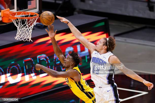Jimmy Butler of the Miami Heat is fouled by Aaron Gordon of the Orlando Magic during the third quarter at American Airlines Arena on March 11, 2021...