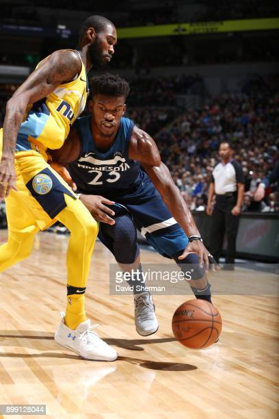 Jimmy Butler of the Minnesota Timberwolves handles the ball against Will Barton of the Denver Nuggets on December 27 2017 at Target Center in...
