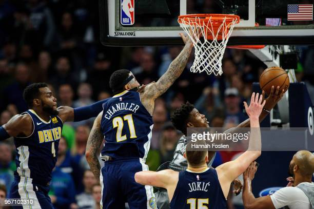 Jimmy Butler of the Minnesota Timberwolves shoots the ball against Paul Millsap Wilson Chandler and Nikola Jokic of the Denver Nuggets during the...