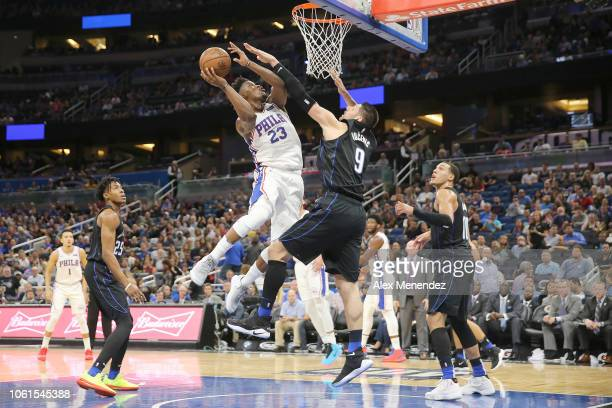 Jimmy Butler of the Philadelphia 76ers drives to the basket against Nikola Vucevic of the Orlando Magic during a NBA game at Amway Center on November...