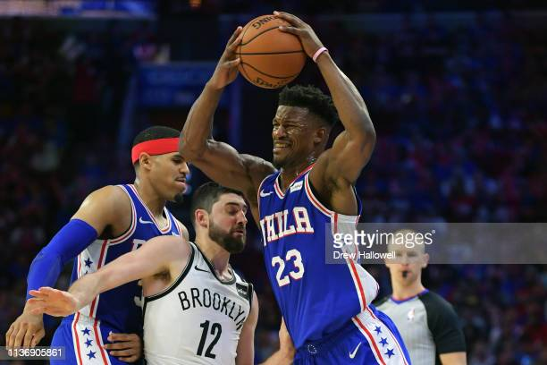 Jimmy Butler of the Philadelphia 76ers gets fouled by Joe Harris of the Brooklyn Nets as Tobias Harris defends in the second half during Game One of...