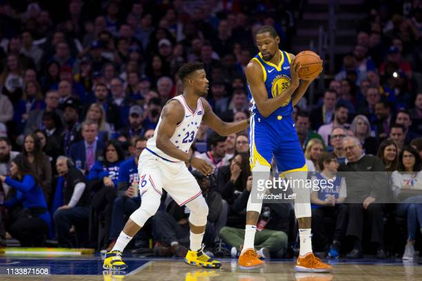 Jimmy Butler of the Philadelphia 76ers guards Kevin Durant of the Golden State Warriors at the Wells Fargo Center on March 2 2019 in Philadelphia...