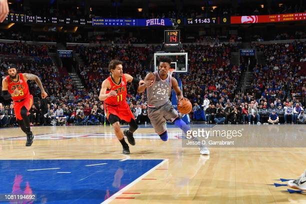 Jimmy Butler of the Philadelphia 76ers handles the ball against Trae Young of the Atlanta Hawks on January 11 2019 at the Wells Fargo Center in...