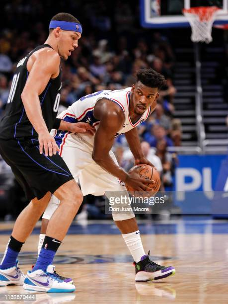 Jimmy Butler of the Philadelphia 76ers is defended by Aaron Gordon of the Orlando Magic during the game at the Amway Center on March 25 2019 in...