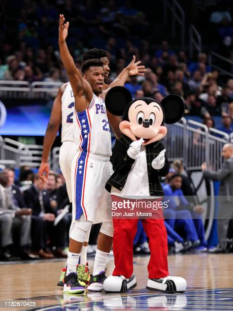 Jimmy Butler of the Philadelphia 76ers strike a pose with Mickey Mouse after a timeout during the game against the Orlando Magic at the Amway Center...