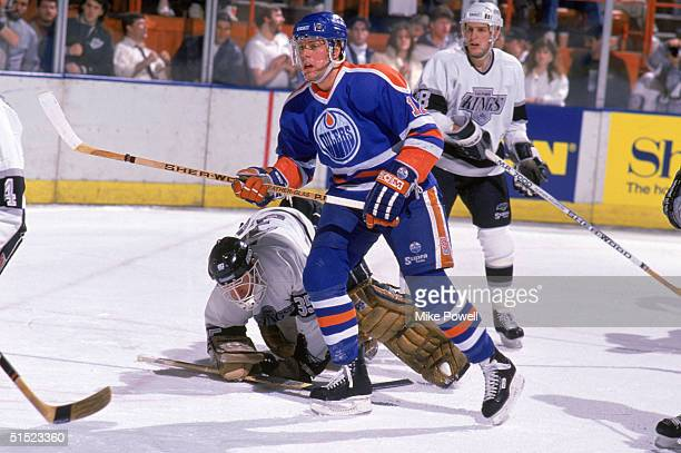 Jimmy Carson of the Edmonton Oilers skates past Los Angeles Kings goalkeeper Rob Stauber who fall out of position in front of the crease during a...