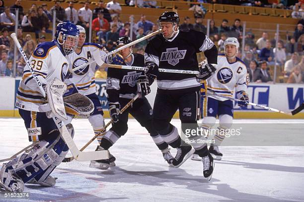 Jimmy Carson of the Los Angeles Kings crashes the net as goaltender Dominik Hasek of the Buffalo Sabres makes a save during a game at Buffalo...