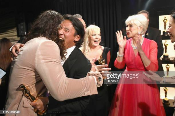 Jimmy Chin and Shannon Dill pose with the Best Documentary Feature award for 'Free Solo' with Jason Momoa and Helen Mirren backstage during the 91st...