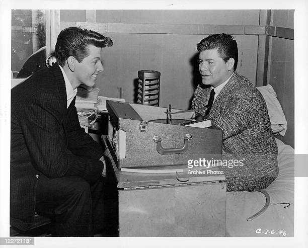 Jimmy Clanton and Ritchie Valens sit across from eat other in a scene from the film 'Go Johnny Go' 1959
