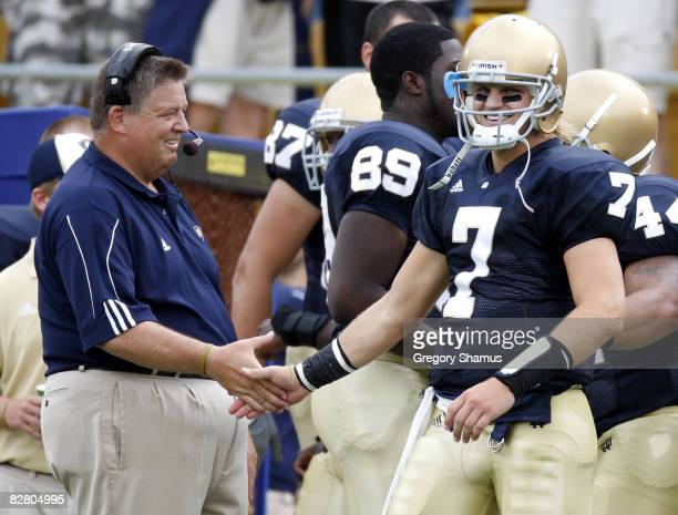 Jimmy Clausen of the Notre Dame Fighting Irish is congratulated by head coach Charlie Weis after a first quarter touchdown against the Michigan...