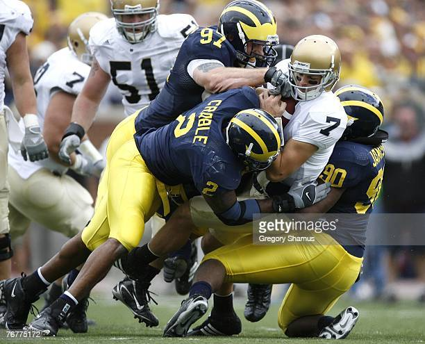 Jimmy Clausen of the Notre Dame Fighting Irish is sacked by Shawn Crable Tim Jamison and Will Johnson of the Michigan Wolverines at Michigan Stadium...