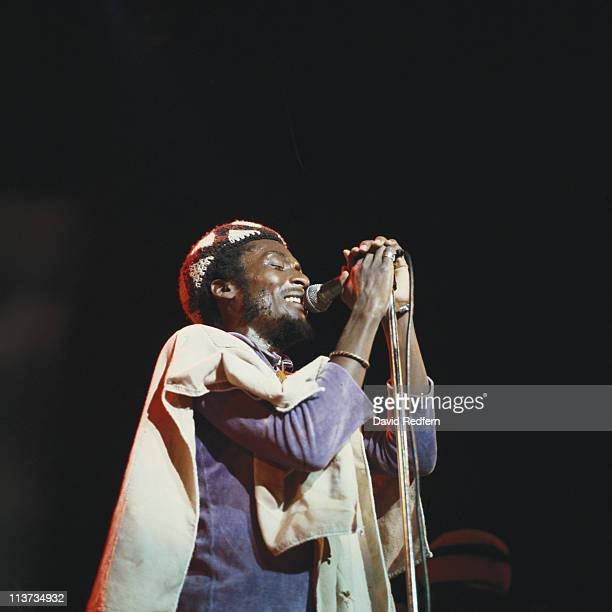 Jimmy Cliff Jamaican ska and reggae singer singing into a microphone during a live concert performance on stage at the Hammersmith Odeon in London...