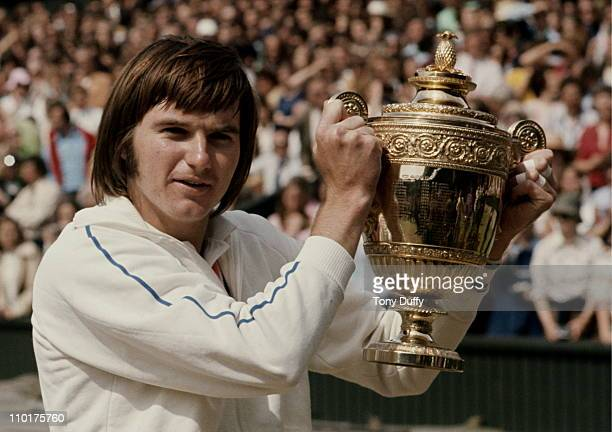 Jimmy Connors of the United States holds aloft the trophy after defeating Ken Rosewall 6–1 6–1 6–4in their Men's Singles final match at the Wimbledon...