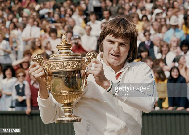 Jimmy Connors of the United States holds the trophy at winning the Men's Singles Final match against Ken Rosewall at the Wimbledon Lawn Tennis...