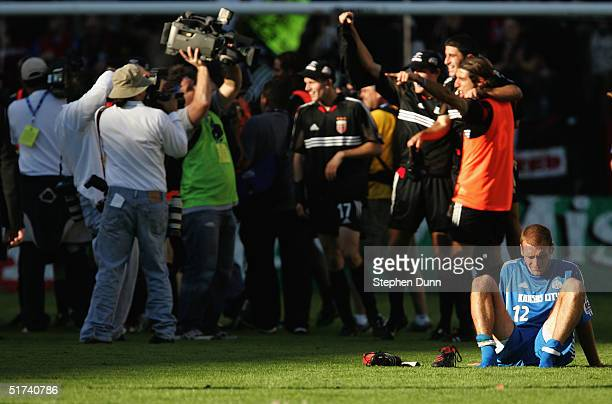 Jimmy Conrad of the Kansas City Wizards sits on the field as the DC United celebrate winning the MLS Cup 32 on November 14 2004 at the Home Depot...