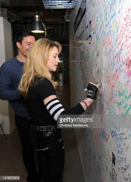 Jimmy Fallon and Madonna sign the Facebook wall before their livestream interview at the Facebook offices on March 24 2012 in New York City