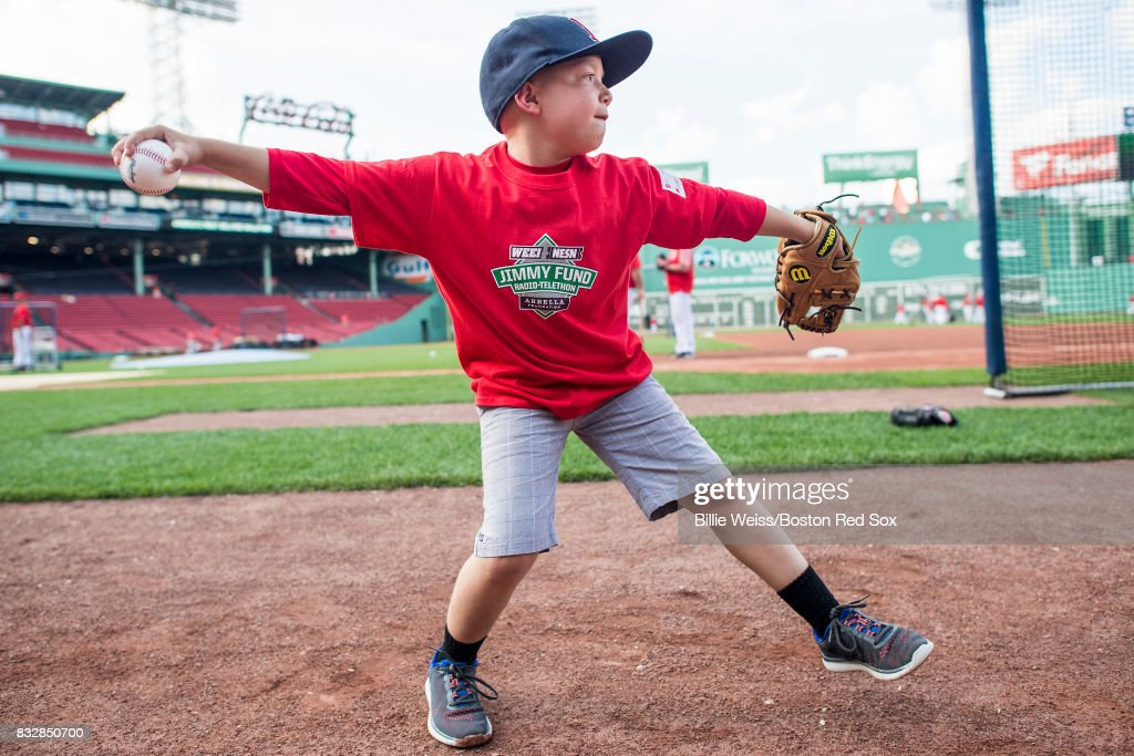 A Jimmy Fund patient plays catch with Brock Holt #12 of the Boston Red Sox before a game against the St. Louis Cardinals on August 16, 2017 at Fenway Park in Boston, Massachusetts.